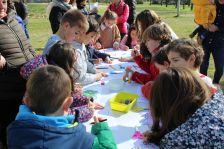 Infants fent un taller de màscares a la primera edició de la Jugatecambiental al parc de la Llacuna